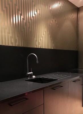 Papier peint, plan de travail en pierre, mitigeur noir, meuble en chêne vernis noir : une cuisine contemporaine