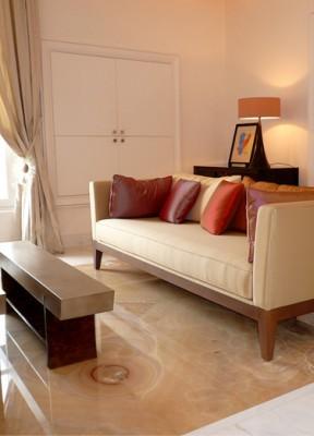 décoration d'un salon haut de gamme : sol en onyxe, canapé contemporain, coussins en soie, meuble gainé de parchemin
